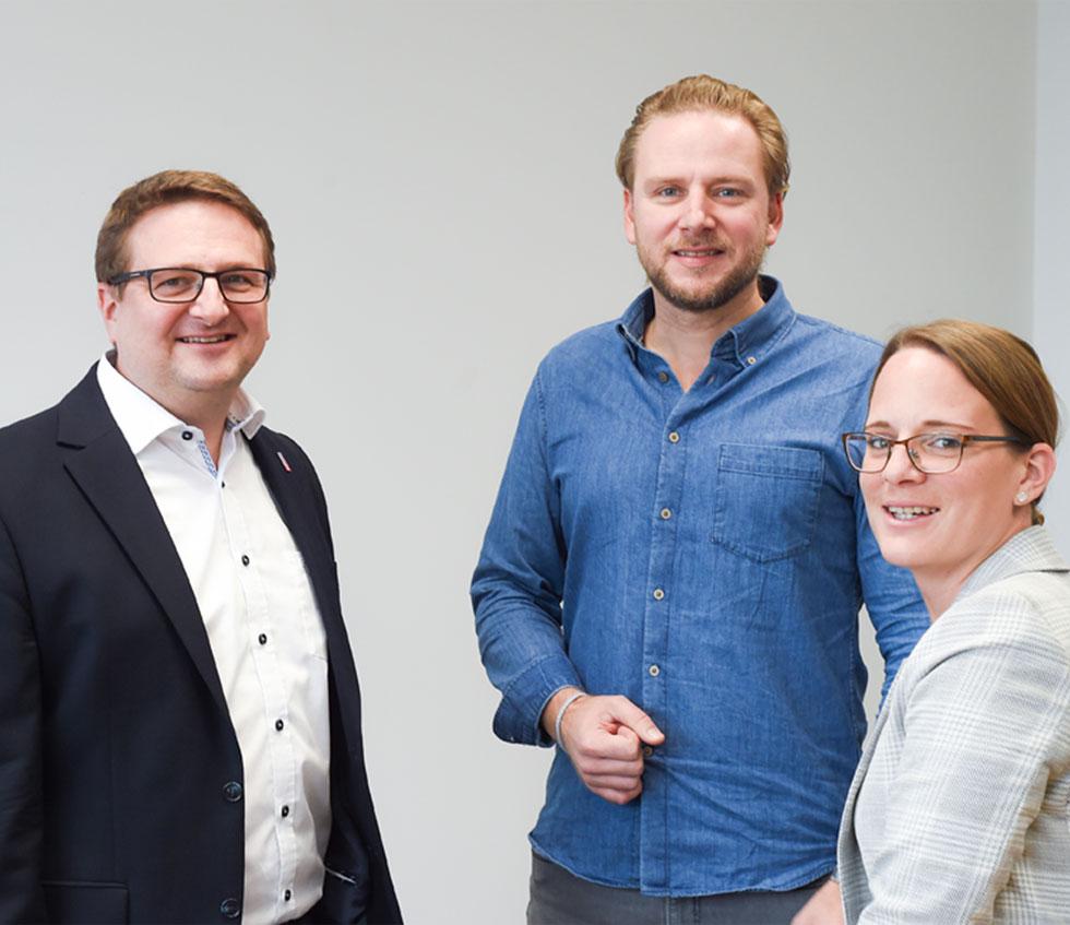 Prokurist, Marketingleiter und Assistentin der Geschäftsführung stehen zusammen